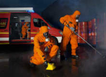 People in orange protection suits cleaning area.
