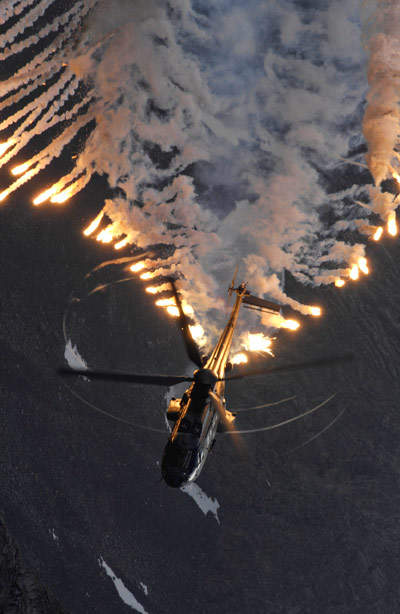 Aerial shot of helicopter deploying flare missiles