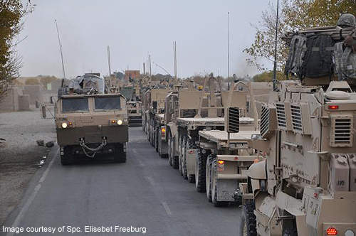 The US Army palletised load system, laden with building materials, passes an empty convoy of PLS trucks and MRAP vehicles.