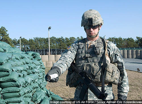 A soldier holds a new M1161A1 hand grenade simulator during a demonstration of the more environmentally friendly training grenades.