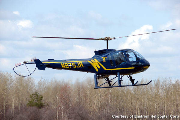 The Enstrom 480B performing agricultural spraying.