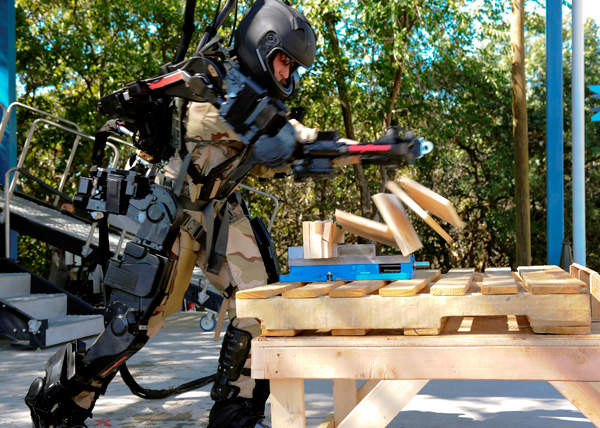 A soldier wearing Raytheon's XOS 2 punching through some wooden blocks during a public demonstration at the research facility in Utah. Credit: Raytheon Company.
