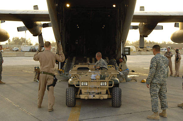 A John Deere M-Gator military utility vehicle being loaded into a C-130 Hercules aircraft at Sather Air Base, Iraq. Image courtesy of US Air Force photo by Tech. Sgt. Jeffrey Allen.