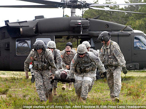 An ambulance crew uses a litter to transport a casualty from a Blackhawk helicopter during eXportable Combat Training Capability exercises.