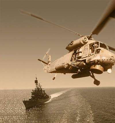 Naval helicopter flying close to a Naval vessel