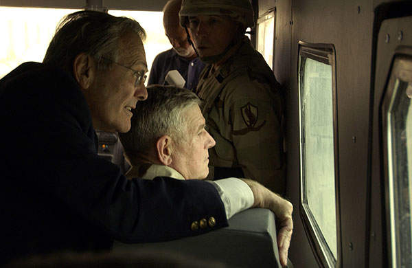 Secretary of Defence Donald H. Rumsfeld and Chairman of the Joint Chiefs of Staff Gen. Richard Myers look at Abu Ghraib Detention Center from inside a RhinoRUNNER bus. Image courtesy of DoD photo, by Tech. Sgt. Jerry Morrison Jr., US Air Force.