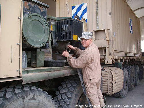 A generator mechanic from the 659th Maintenance Company's palletised load system maintenance support team works on a PLS.