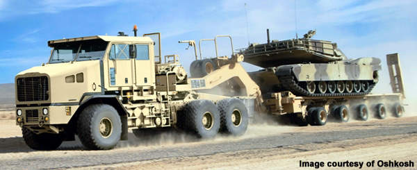 A Oshkosh 1070F Heavy Equipment Transporter carrying a tank