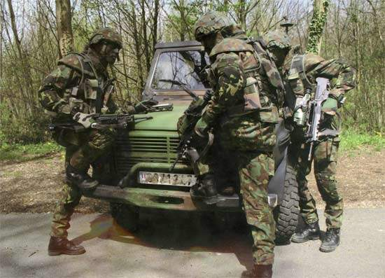 Three FELIN soliders inspecting a vehicle