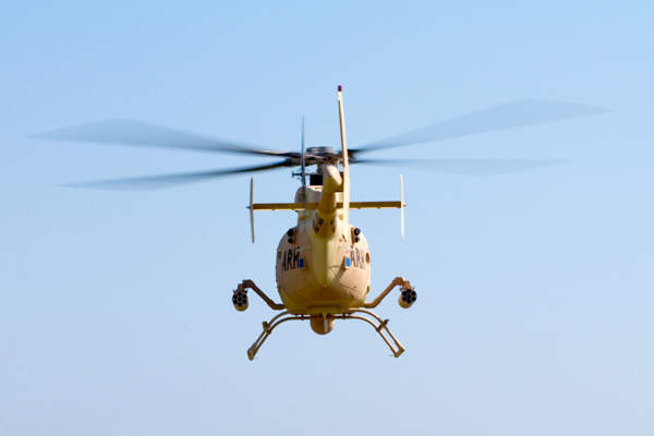 The ARH-70A helicopter flying away armed with two side guns