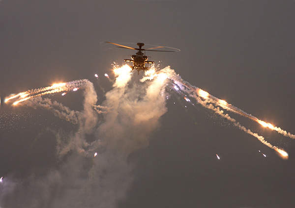 An Apache AH Mk1 helicopter launches chaff and flare countermeasures.