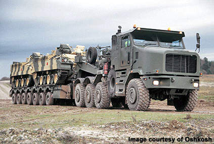 A Oshkosh 1070F Heavy Equipment Transporter carrying two tanks
