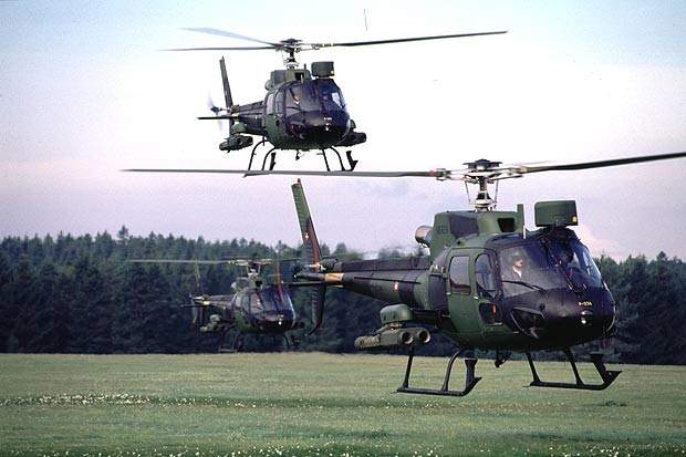 Three AS 555 Fennec single-engine helicopter in flight formation