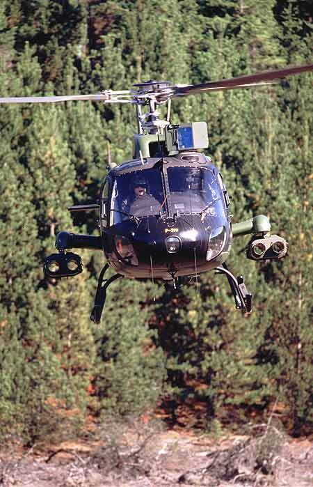 The AS 550 helicopter in flight over a forested area