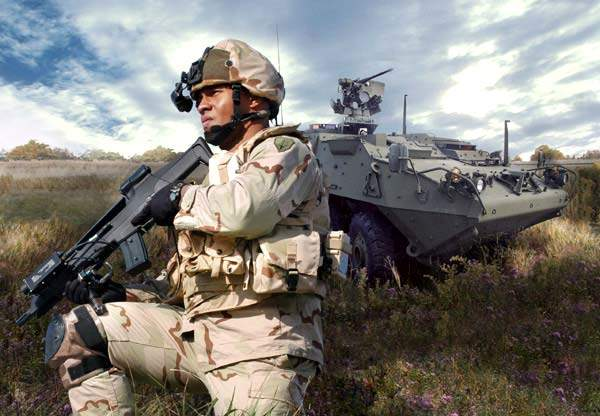 Land warrior soldier in front of a Stryker armed vehicle