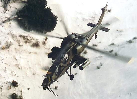 AW129 helicopter flying over snowy terrain