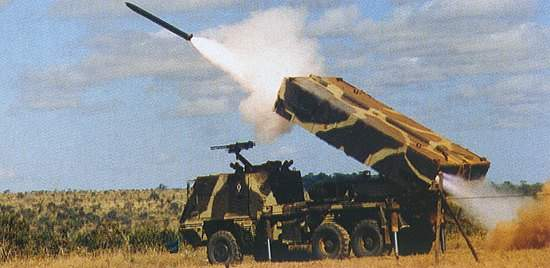 Camouflaged Astros II artillery system firing a rocket