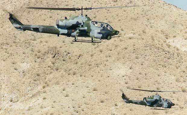 Two Super Cobra attack helicopters in flight formation.