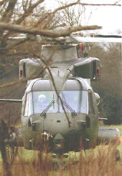 An AW101 helicopter lifting a military truck