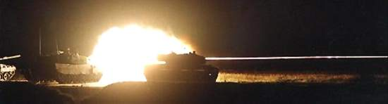 Leopard 2A4's shooting at night on a practice range in Germany.