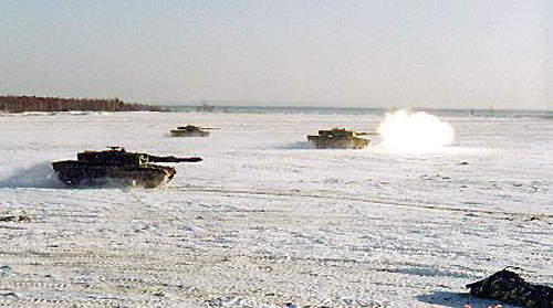 Several Leopard 2 tanks on exercise in the snow.