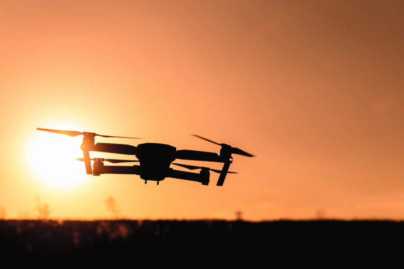 Drone silhouette with camera flying in the sunset light