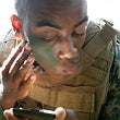U.S. Marine Corps Cpl. Emery Williams looks at a mirror as he applies camouflage paint on his face at Marine Corps Base Hawaii, May 19, 2010.